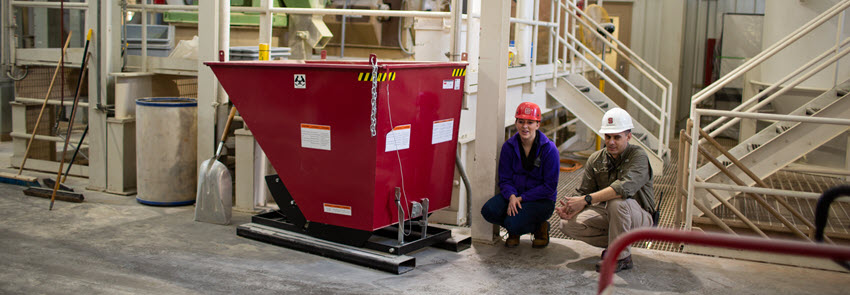 Two faculty members crouch down next to a red container at the feed mill.