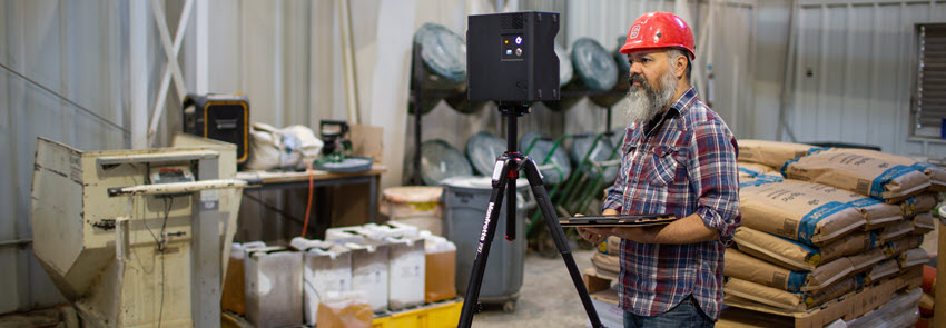 A DELTA Staff member mans a camera on a tripod in the feed mill.