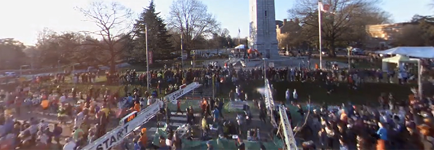 Runners pass through the starting line in front of the NC State Bell Tower.