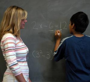 Teacher helps student work on math problem on a chalkboard.