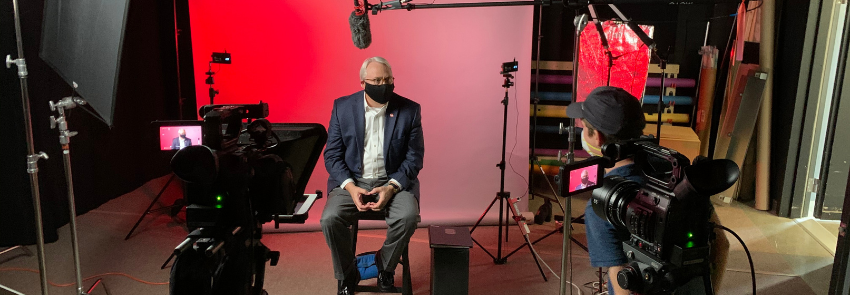 Chancellor Randy Woodson films a video for the Wicked Problems, Wolfpack Solutions course. He is pictured in front of a camera with producer Todd Buker instructing.