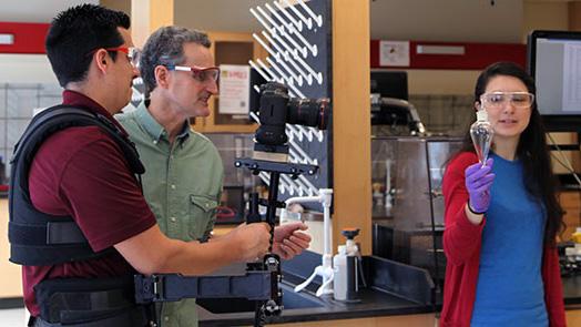 DELTA staff members Michael Castro, left, and John Gordon shoot video of student Christina Schaefer inside a lab.