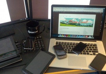 View of multiple devices on a desk of different sizes, including smartphones, tablets, a laptop, and monitors