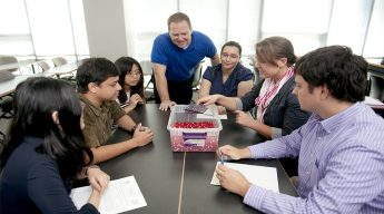 Dr. Roger Woodward works with statistics students on an activity.