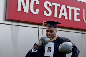 Brian McCluney in graduation attire and boxing gloves in front of the NC State University sign.