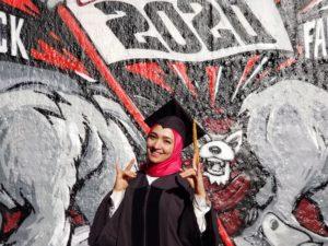 Hadir Eldeeb in graduation attire in front of a mural