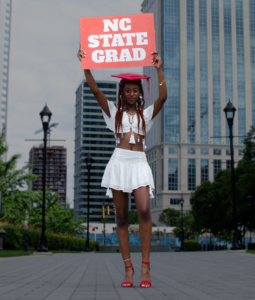 "Nakyrah Radney in a graduation cap holding a sign that reads ""NC State Grad"""