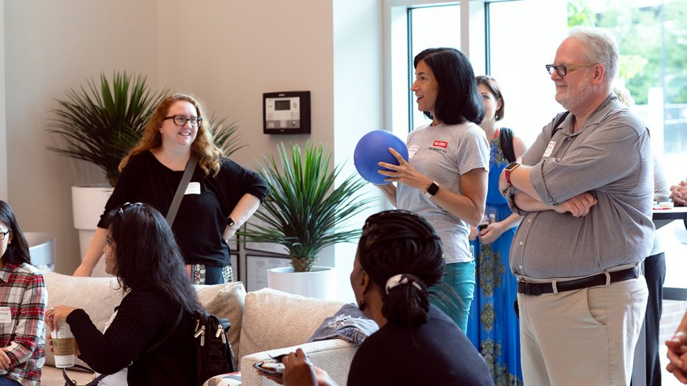 Director of Professional Development at the Career Development Center Marcy Bullock (center) speaks to participants at DELTA-Con in May. Bullock is holding a blue ball microphone and participants are actively looking at her. Photo in the CTI lobby.