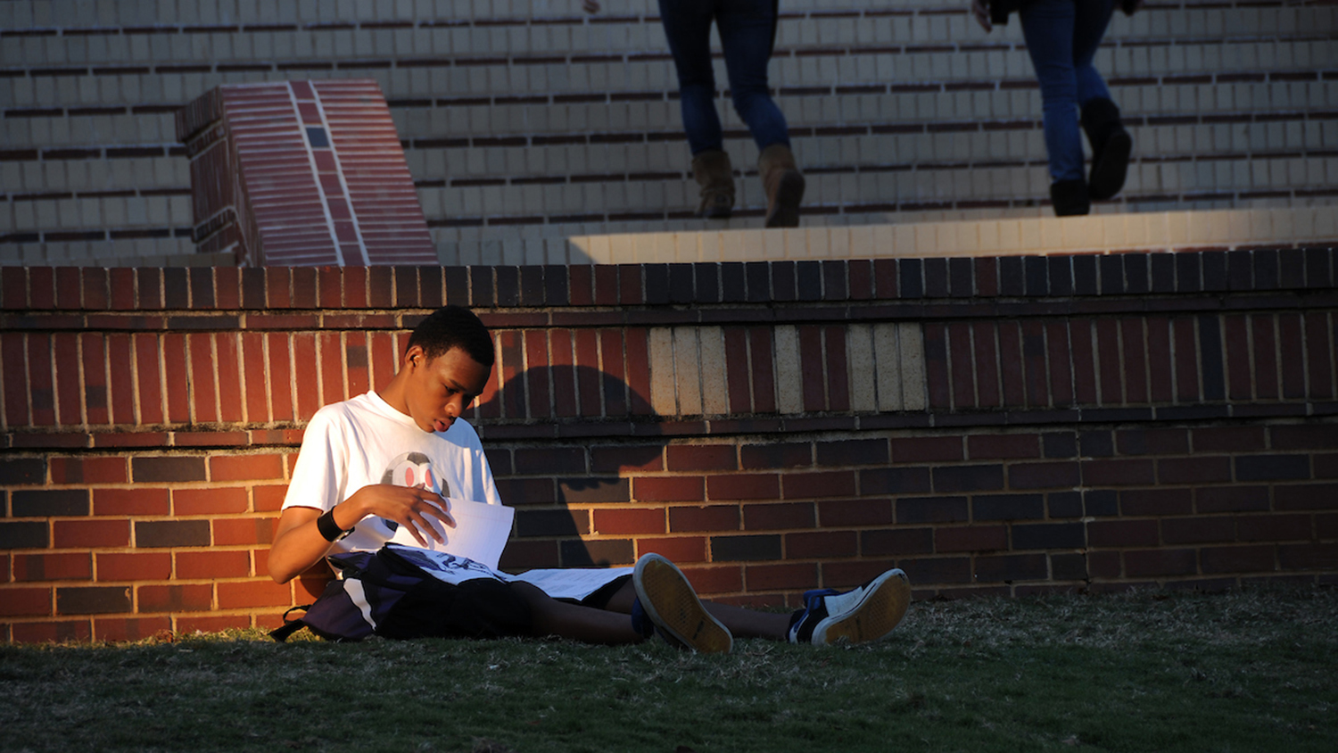Setting sun reflects upon a student studying on the Court of North Carolina.