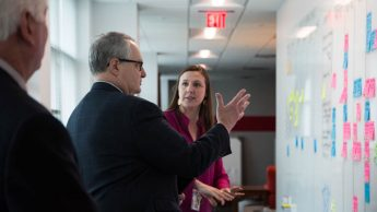 Photo of Merranie Zellweger discussing project coordination with Provost Arden