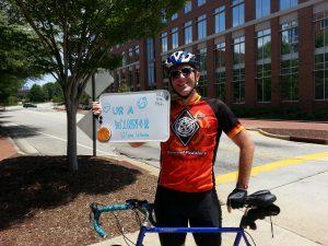 Photo of Ben Huckaby standing beside his bicycle