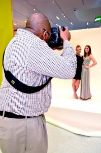 Photo of Emanuel Brunson photographing models for the College of Textiles Threads Senior Collection show.