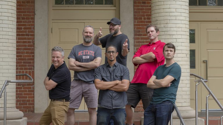Group photo of DELTA's College of Design alumni in front of Leazar Hall on NC State's campus.