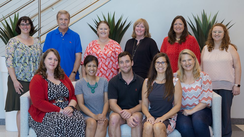 Photo of OCIP team in the CTI lobby. Back row is standing behind the front row who are seated on a couch. Back row, left to right: Molly Fenn, David Shew, Leigh Shamblin, Christine Cranford, Angie Smith, Kim Allen. Front row, left to right: Bethany Smith, Arelene Mendoza-Moran, Christopher Beeson, Bethanne Tobey, Rebecca Sanchez. Photo by Katie Harris.