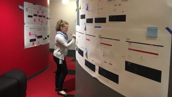 Jen Pettit reviews WolfWare wireframes as part of the WolfWare redesign and usability project. Printouts of wireframes are seen on the walls of DELTA offices.