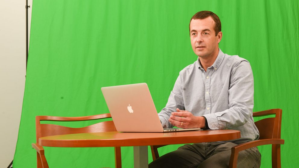 Clint Stevenson sitting at a table with a laptop in front of a green screen.
