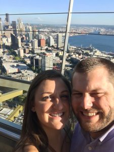 Naomi and Vince Lastreto at the top of the Space Needle. Vince and Naomi smile together in a selfie.