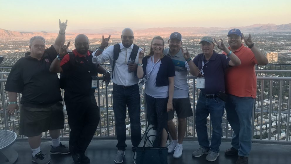 Left to right: Darren Ley, Tony Pearson, Shawn Colvin, Donna Petherbridge, Tim Hinds, Bob Klein and Brandon Pope in Las Vegas for the UBTech conference and InfoComm trade show. The group is standing on a balcony in front of the skyline.