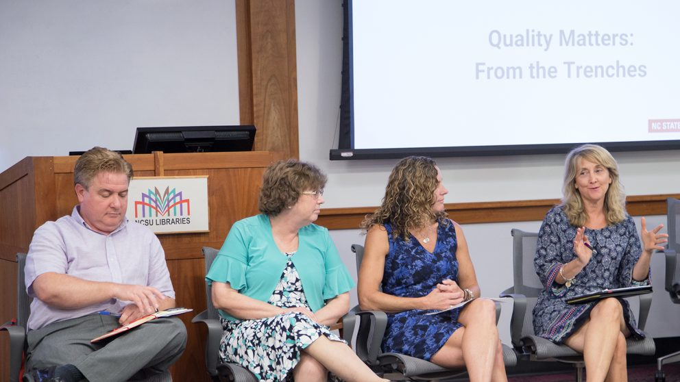 Members of the first cohort of the Online Course Improvement Program facilitated a panel discussion at Summer Shorts 2018. Pictured left to right: Paul Mulvey, Cheryl Block, Amanda Edwards and Tracy Appling. Not pictured: Marne Coit, Ana Gray and Jill Grifenhagen. The group sits in front of the audience. Tracy Appling is speaking and the other OCIP members are looking at her.