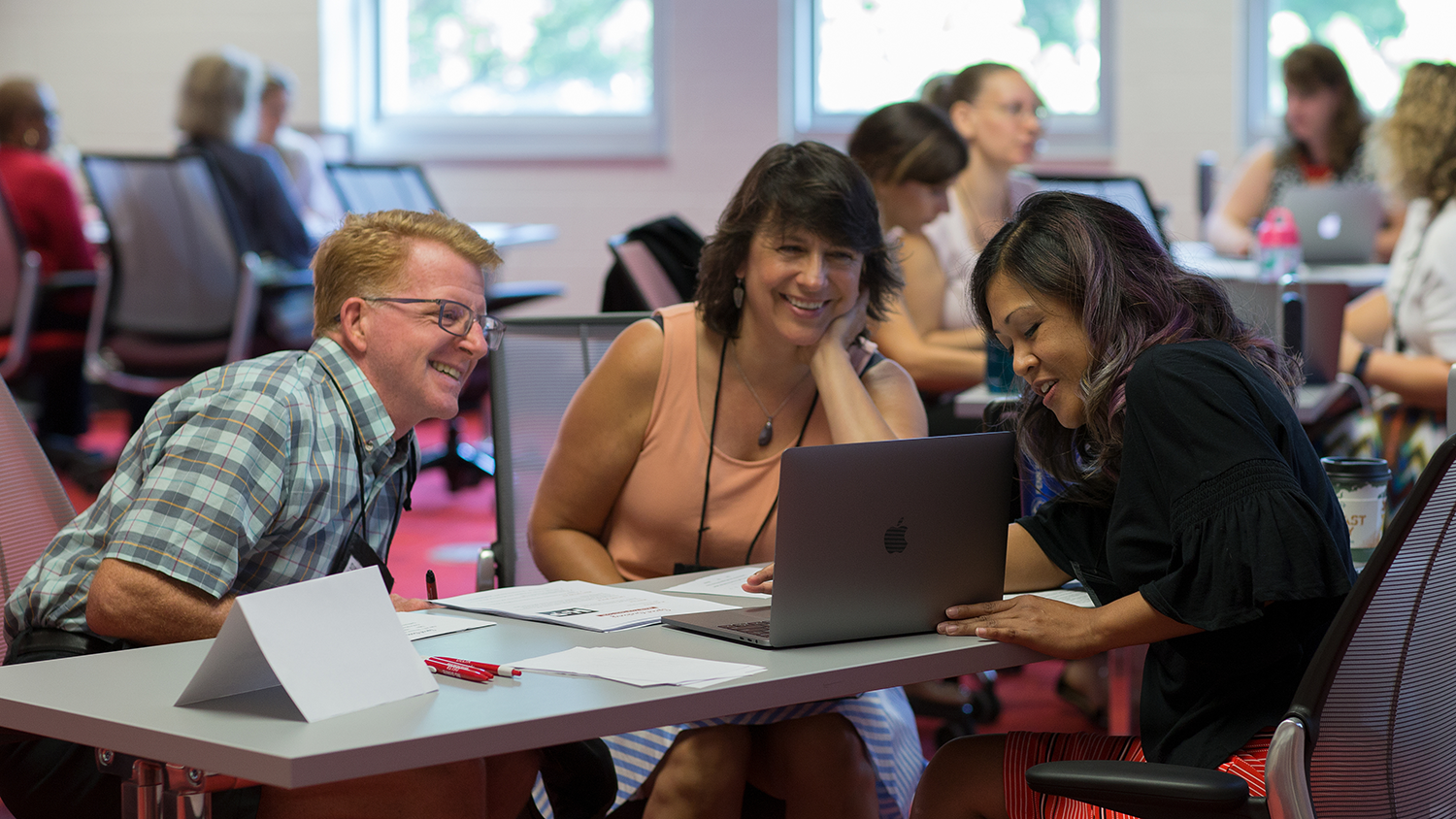 Arlene Mendoza-Moran (right) works with faculty at the 2018 Summer Shorts in Instructional Technologies program. Mendoza-Moran and faculty are working on a laptop at a desk.