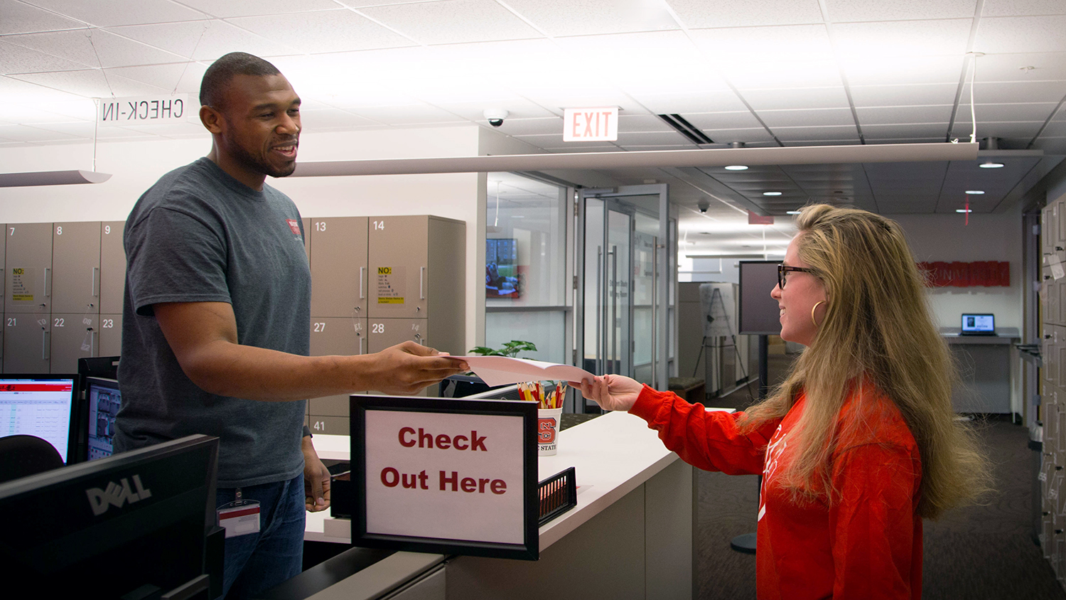 DELTA Testing Services Associate Brad Collins (left) pictured with a student who is turning in a test at the Centennial Campus Test Center.