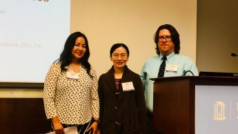 DELTA Staff members (left to right) Jakia Salam, Yan Shen and Chris Willis at the 2019 UNC System Student Success Conference. The group is standing in front of a screen and behind a podium at the conference.