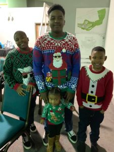 Tamara's four kids posed smiling in Christmas sweaters.