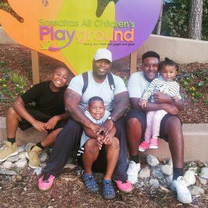 Tamara's husband Jonathan sitting outside with their four children, Jaidyn, Jordyn, Gavin and Gabby, smiling