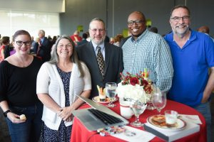 Sherry and other DELTA staff members at the 2018 NC State Awards for Excellence reception. Left to right: Janna Martin, Sherry O'Neal, Jeff Webster, Emanuel Brunson and Marty Dulberg. The group is pictured around a table.