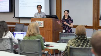 Instructional Designer Yan Shen (right) gives a presentation at the 2018 Summer Shorts. Yan is pictured at the front of the room with participants in the crowd.