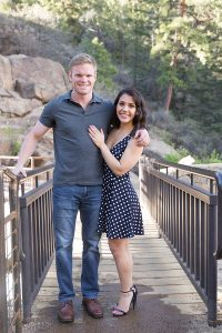 Monica and her husband, Kevin, pictured posing together on a bridge in nature.