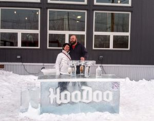 "Brandon and wife, Melissa, smiling behind an ice bar labeled ""HooDoo"" and surrounded by snow."