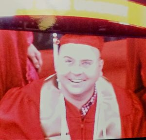 Brandon smiling on a Jumbotron screen in graduation cap and gown.