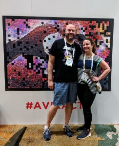 Brandon and wife, Melissa posing in front of a poster at Infocomm with lanyards.