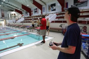 Buker handles a remote control to fly a drone over a swimming pool inside the Aquatic Center