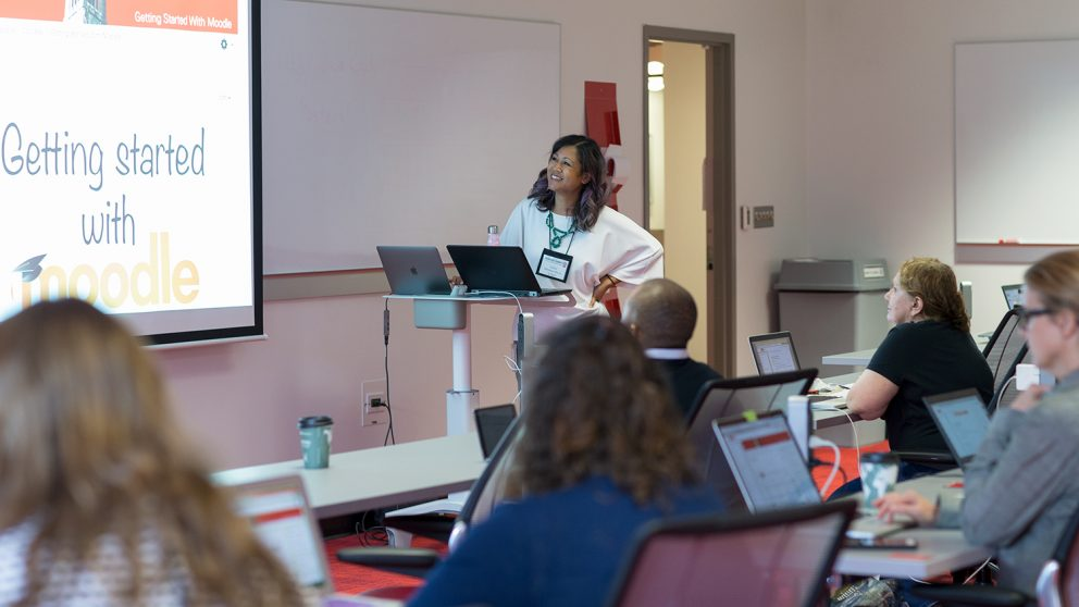 Instructional Technologist Arlene Mendoza-Moran leads a session about Moodle at the 2018 Summer Shorts in Instructional Technologies program. Arlene is at the front of a classroom looking at a screen that says
