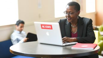 Woman sits at a table with a laptop and notebook. Laptop has NC State sticker.