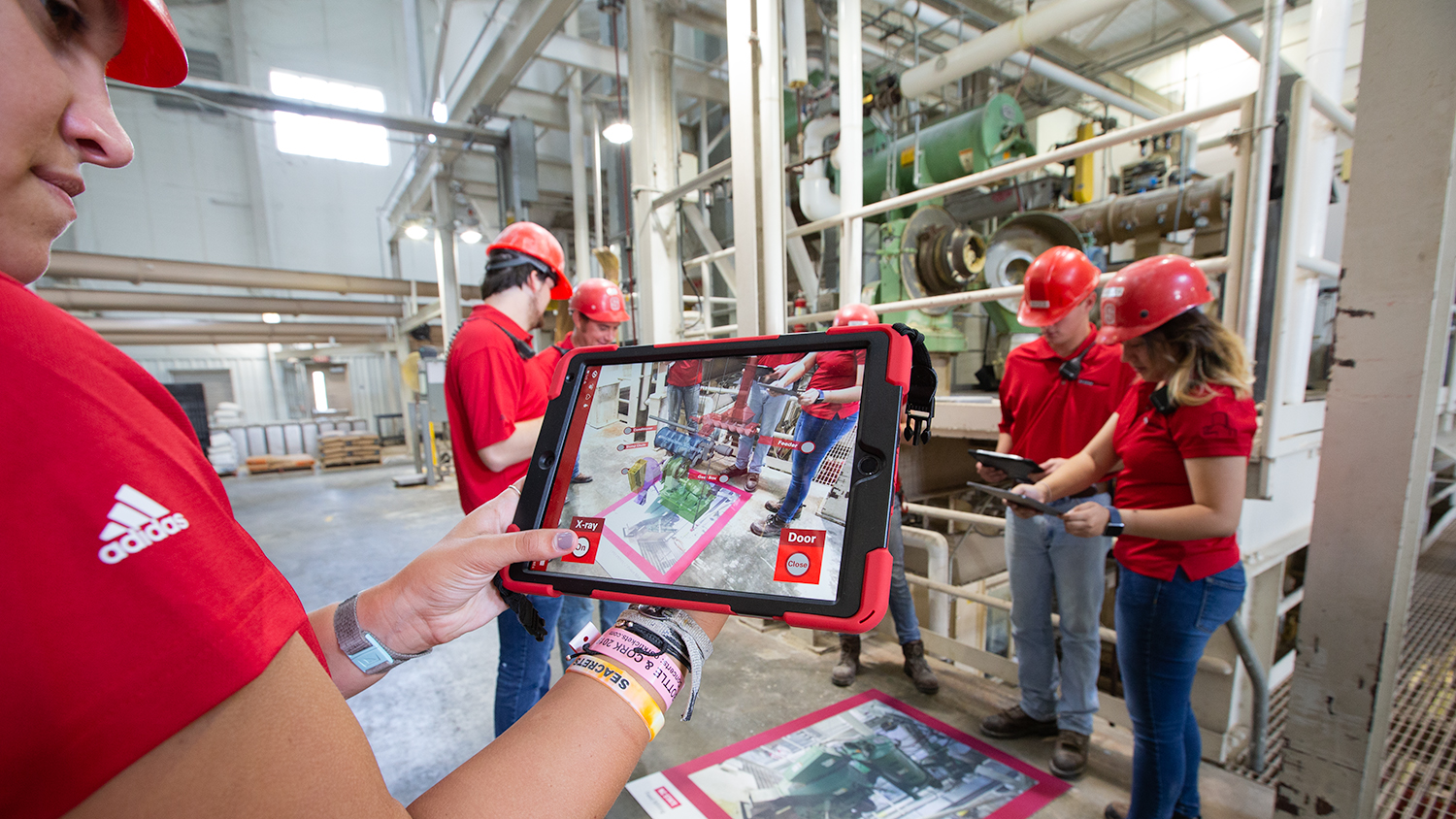Taken inside the feed mill, a person holds a tablet with the AR experience loaded. There are other students gathered around a map of the Feed Mill and on the screen you can see the AR experience on the mat.