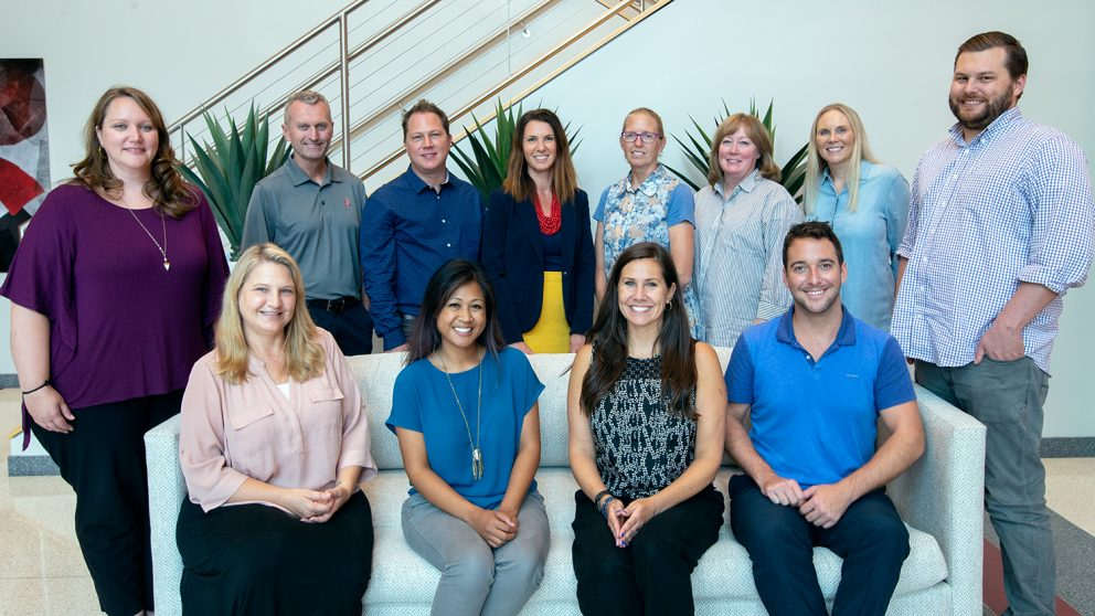 The fall 2019 OCIP team and faculty cohort. Front row, left to right: Rebecca Sanchez, Arlene Mendoza-Moran, Bethanne Tobey, Christopher Beeson. Standing, left to right: Bethany Smith, Michael Kanters, Seth Murray, Wendy Warner, Melissa Hendrickson, Christine Cranford, Julianne Treme, Vince Lastreto. Not pictured: Jamie Larsen. Photo by Katie Harris. The front row is sitting on the couch in the CTI lobby and the back row is standing behind them.