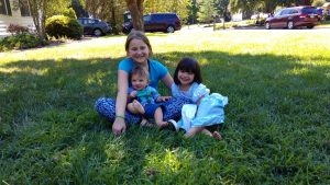 Lynda's grandchildren, Addie, Ida and Teddy. They are sitting on the grass together.