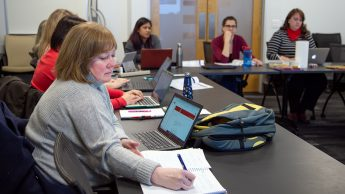 Christine Cranford writes down important notes during a face-to-face meeting of the Online Course Improvement Program in spring 2019. Christine is sitting at a table with other people in the distance.