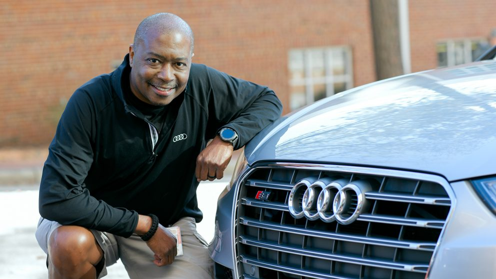 Jeff Robinson posing with his car. He is kneeling down beside the front of his Mercedes.