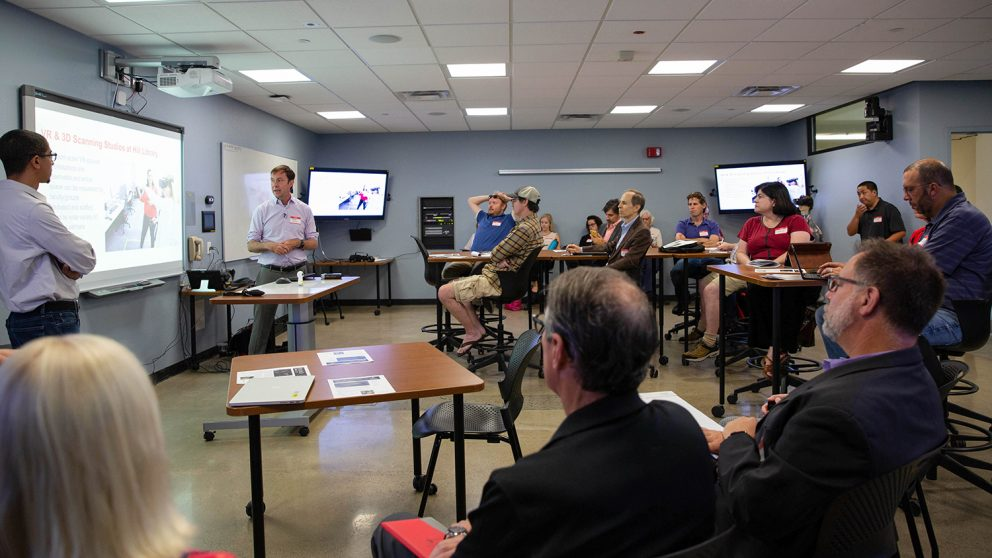 Mike Cuales (front left) and David Woodbury (front right) give a presentation at San Diego State University about immersive learning technologies and spaces. Cuales and Woodbury are at the front of the room and there are participants sitting at tables engaged in their presentation.