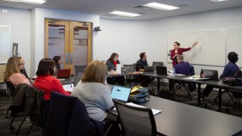 Course Quality Program Director Bethanne Tobey leads an Online Course Improvement Program meeting. Group is around tables and Bethanne is writing on a white board.