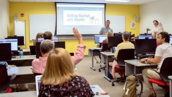 Christopher Beeson and McLean Lucas stand at the front of a computer lab room. There are participants at computer stations around the room. One participant is raising his hand. The screen says