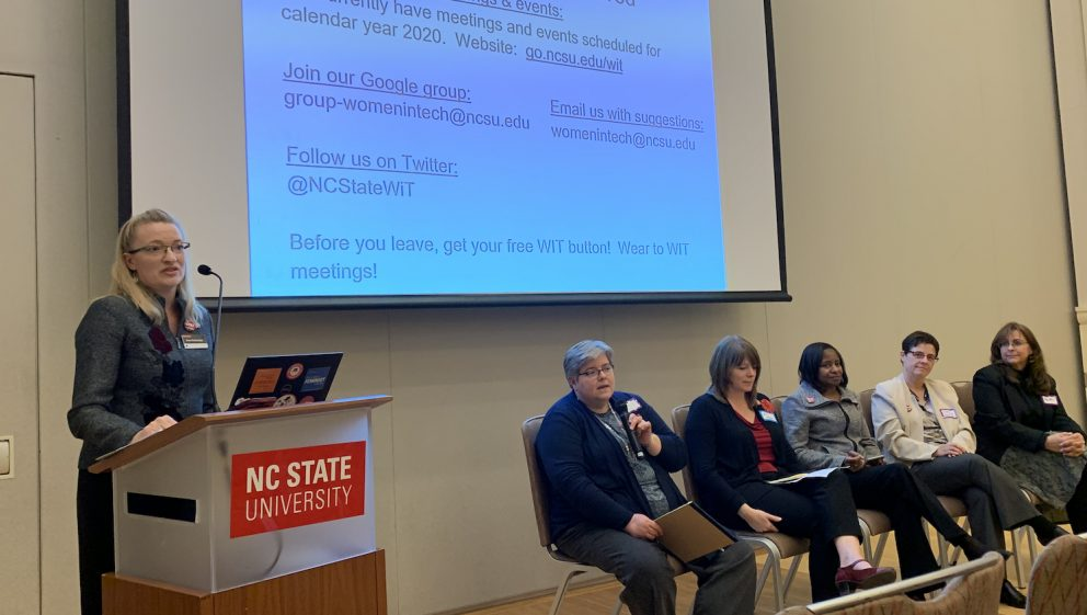 The Women in Technology (WIT) interest group kicked off at the 2019 IT Community Event. Donna Petherbridge (far left) facilitates a leadership panel with other members of the WIT steering committee. Pictured left to right: Susan West, Jill Sexton, Mardecia Bell, Debbie Carraway, and Gwen Hazelhurst. Donna Petherbridge is at a podium and the other members are sitting in chairs at the front of the room.