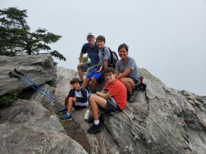 Arlene posed with her husband and their three sons on a rocky landscape at Hanging Rock State Park.