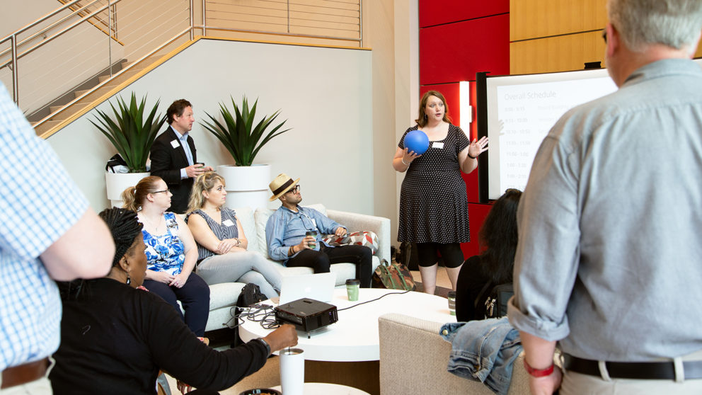 Bethany Smith stands in the middle of a group holding a blue microphone ball. Attendees sit and stand around listening to her. Photo is in the CTI lobby.