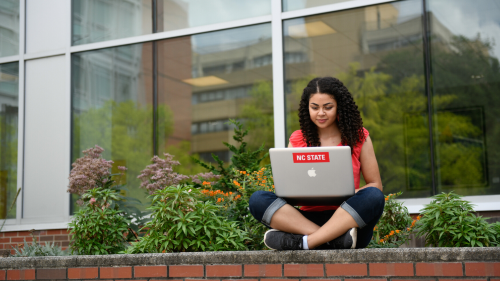 Young woman sitting on a brick ledge with a laptop in front of large windows and greenery.