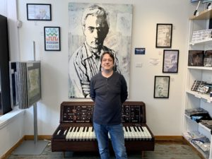 Scott Leonard stands in front of a piano and a painted portrait.